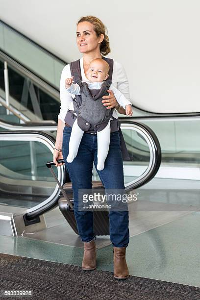 Woman traveller carrying a baby  at the airport
