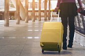 Woman traveller with travel bag or luggage walking in airport terminal walkway for travel abroad.