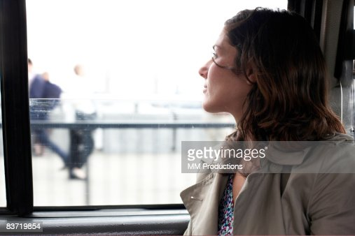 Woman travelling in taxi looking out of window : Stock Photo