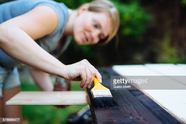 Woman treating a wood board.