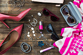 Woman Trendy Fashion Accessories such as Court Shoes, Scarf, Sunglasses, Pen Lipstick,  Nail Polish, Purse, and Jewellery on Rustic Wooden Background, Flat Lay, Top View