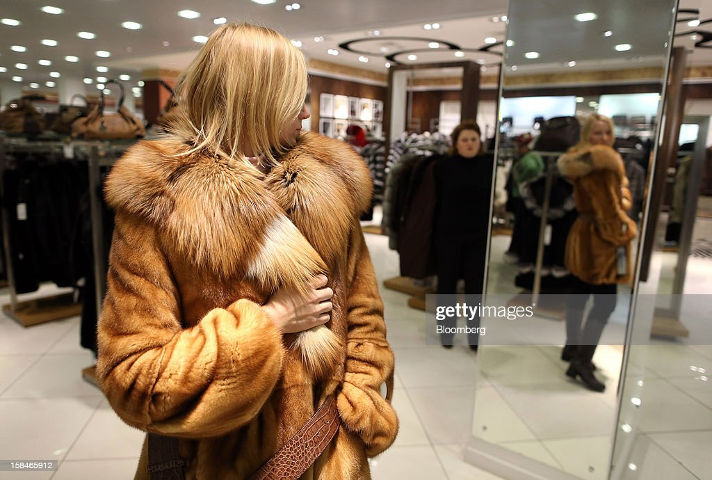 A woman tries on a fur coat in this arranged photograph at the World of Fur and Leather store in Moscow, Russia, on Sunday, Dec. 16, 2012. Russia's government should introduce a tax on luxury consumption in first half of 2013, President Vladimir Putin said in state-of-the-nation address in Moscow. Photographer: Andrey Rudakov/Bloomberg via Getty Images