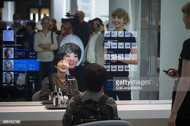 A woman tries on different make up options in the mirror at the booth of the Japanese electronics giant Panasonic on the opening day of the 55th IFA...