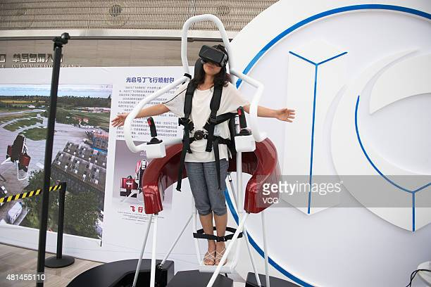A woman tries on Martin Jetpack simulator during an innovator conference organized by KuangChi Innovative Technology Ltd at Shenzhen Poly Theatre on...