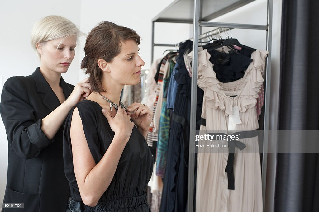 Woman tries on necklace with shop keeper's help : Stock Photo