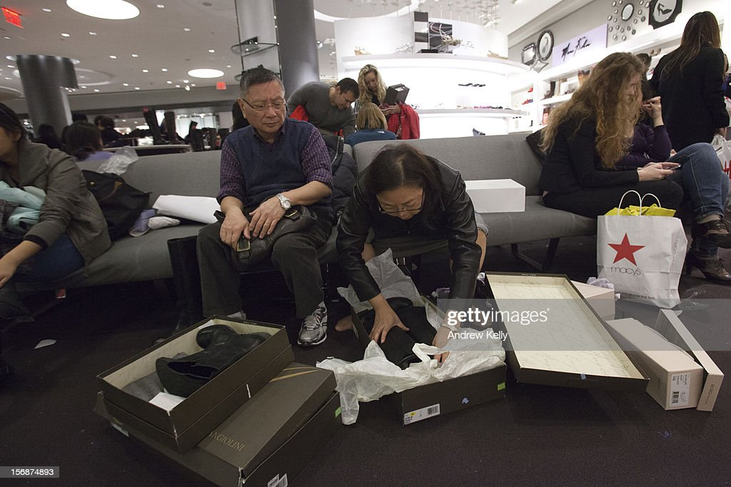 A woman tries on shoes in Macy's during the Black Friday sales on November 23, 2012 in New York City. Shoppers filled stores in search of the many potential bargains on offer during the traditional yearly sale, which got its name as it's said to put retailers 'in the black,' or making a profit.