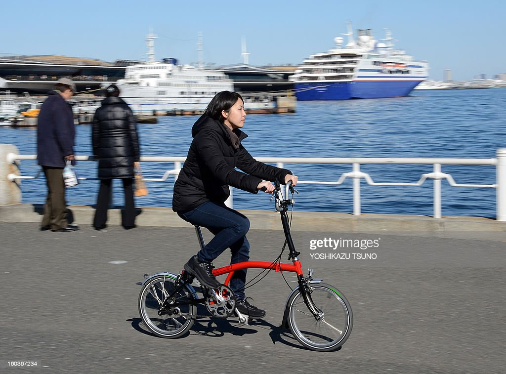 A woman tries out a Brompton folding bicycle in Yokohama, in Japan, on January 27, 2013. British bicycle company Brompton produced 36,000 bikes in 2012 with a turnover of around GBP 20m (approx 23.25m euros). Brompton's folding bikes have proved popular with customers in Asian countries such as Japan. AFP PHOTO / Yoshikazu TSUNO