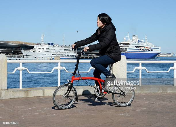 A woman tries out a Brompton folding bicycle in Yokohama in Japan on January 27 2013 British bicycle company Brompton produced 36000 bikes in 2012...