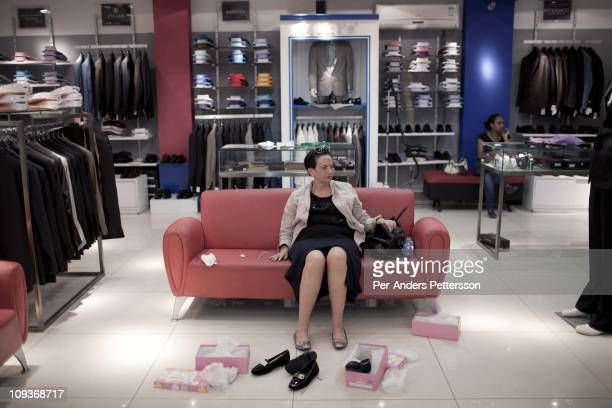 A woman tries shoes in an upmarket clothing shop on November 13 2010 in a shopping mall in Addis Ababa Ethiopia Some people can afford to buy...