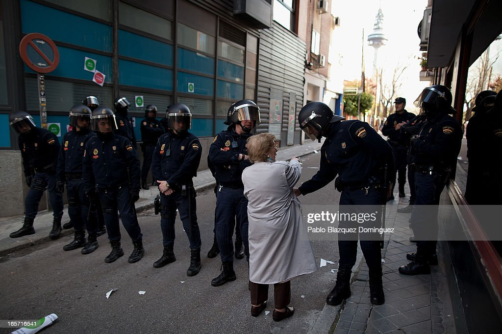 A woman tries to cross a police line during an 'escrache' outside the house of Spain's First deputy prime minister and government spokeswoman Soraya Saenz de Santamaria on April 5, 2013 in Madrid, Spain. The Mortgage Holders Platform (PAH) and other anti evictions organizations have been organizing 'escraches' for several weeks under the slogan 'There are lives at risk' to claim the vote for a Popular Legislative Initiative (ILP) to stop evictions and facilitate social rent, outside Popular Party deputies' houses and offices. 'Escraches' are a form of peaceful protest that were used in Argentine in 1995 to publically denounce pardoned members of the dictatorship for their crimes at their doorsteps.