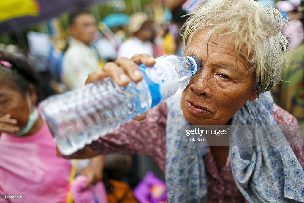 A woman tries to flush tear gas out of her eyes after Thai police gassed the crowd during a large anti government protest on November 24, 2012 in Bangkok, Thailand. The Siam Pitak group, which sponsored the protest, cited alleged government corruption and anti-monarchist elements within the ruling party as grounds for the protest. Police used tear gas and baton charges againt protesters.