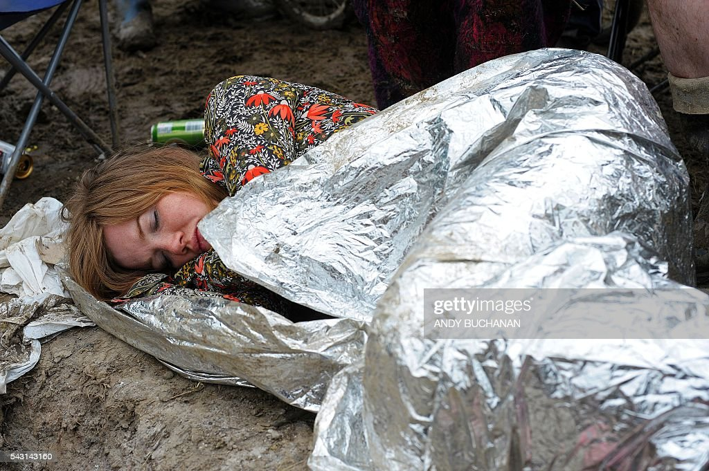 A woman tries to get some sleep on day five of the Glastonbury Festival of Music and Performing Arts on Worthy Farm near the village of Pilton in Somerset, South West England on June 26, 2016. / AFP / Andy Buchanan