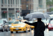 A woman tries to hail a cab in the rain on Lexington Avenue on the east side of Manhattan May 16 2014 in New York The city is under a flash flood...