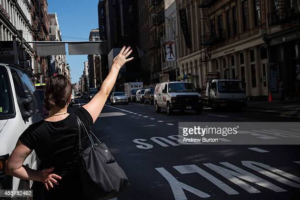 A woman tries to hail a cab on Broadway near the construction site at 42 Crosby Street which is being developed into a luxury apartment building with...