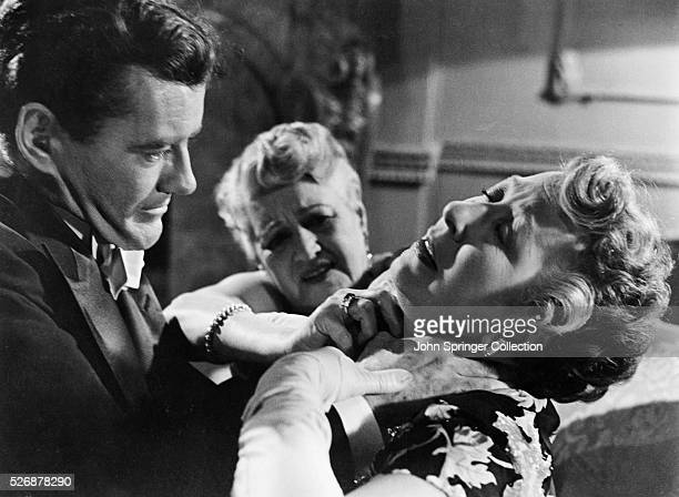 A woman tries to pry the hands of Bruno Antony from the neck of another woman in a scene from Alfred Hitchcock's classic thriller Strangers on a Train