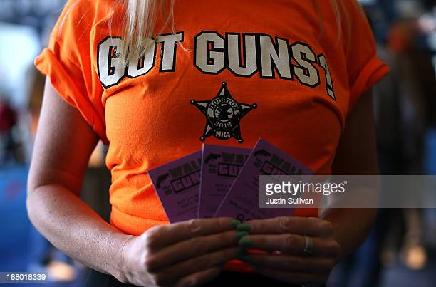 A woman tries to sell raffle tickets to win a gun from the 'Wall of Guns' during the 2013 NRA Annual Meeting and Exhibits at the George R Brown...