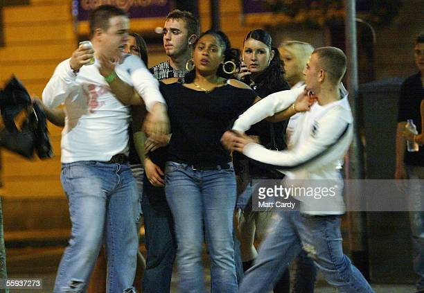 A woman tries to seperate two men during a disagreement in Bristol City Centre on October 15 2005 in Bristol England Pubs and clubs are preparing for...