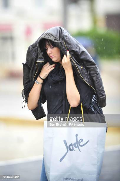 A woman tries to shield her hair and face from the rain as she walks through Bristol city centre as heavy rain is expected to drench most of the UK