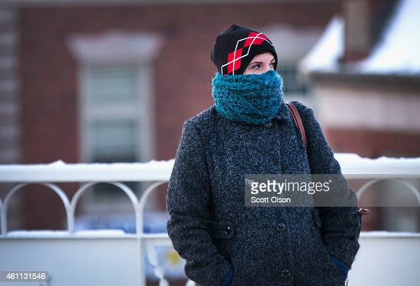 A woman tries to stay warm as she waits on an L platform during the early morning rush while temperatures hovered around zero degrees Fahrenheit on...