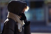 A woman tries to stay warm while waiting for a bus in Coney Island during subzero cold weather in the Brooklyn borough on January 7 2014 in New York...