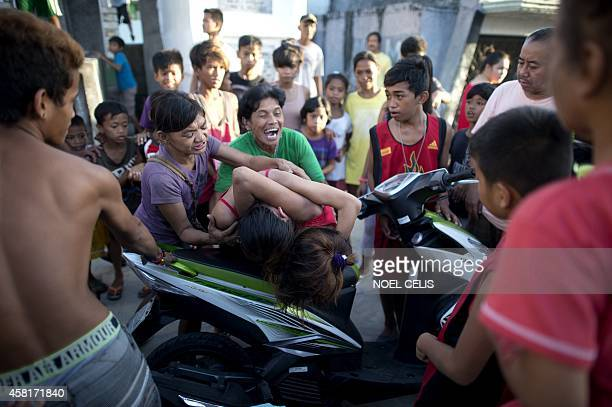 A woman tries to stop girls who live inside the cemetry as they fight biting scratching each other's faces and pulling hair at the Navotas Public...