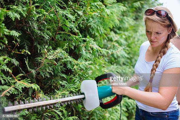 Woman trimming a hedge.