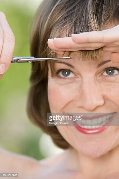 Woman trimming her fringe