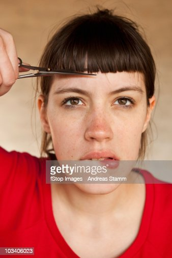 A woman trimming her own bangs