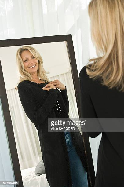 Woman trying on a dress in front of a mirror