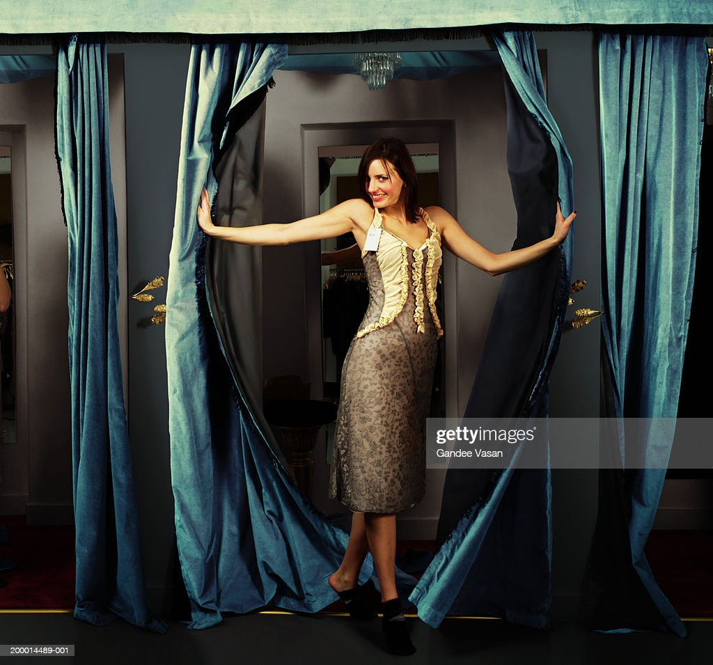 Woman trying on dress in changing room, smiling, portrait : Foto de stock