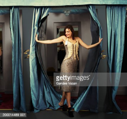 Woman trying on dress in changing room, smiling, portrait