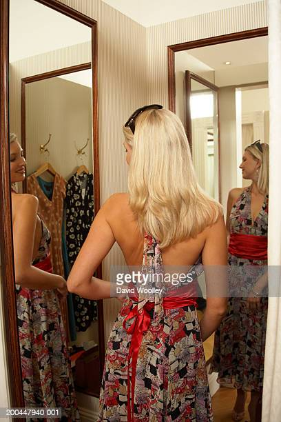 Woman trying on dress in store changing room, rear view
