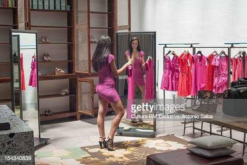 Woman trying on dresses in shop