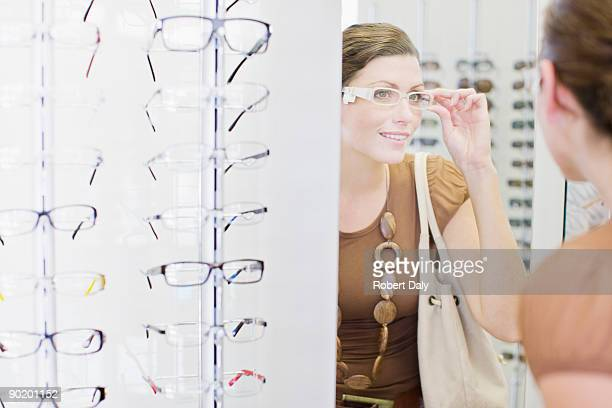 Woman trying on glasses in optometrists shop