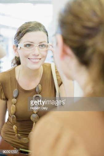 Woman trying on glasses in optometrists shop : Stock Photo
