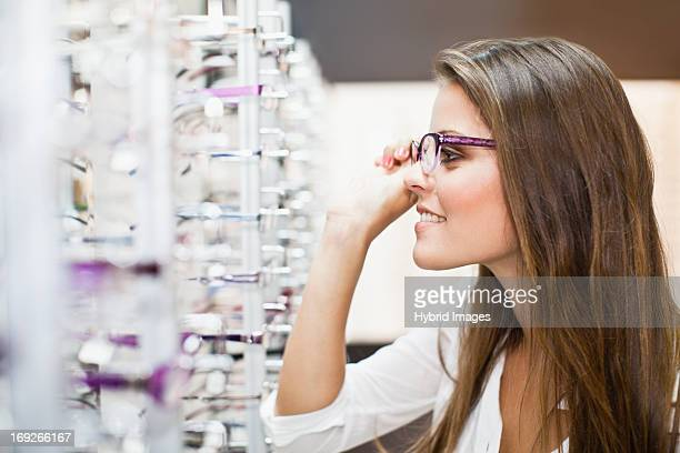 Woman trying on glasses in store