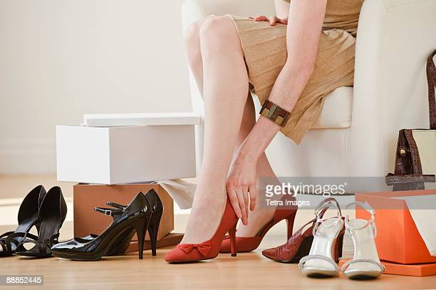 Woman trying on high heel shoes in shop