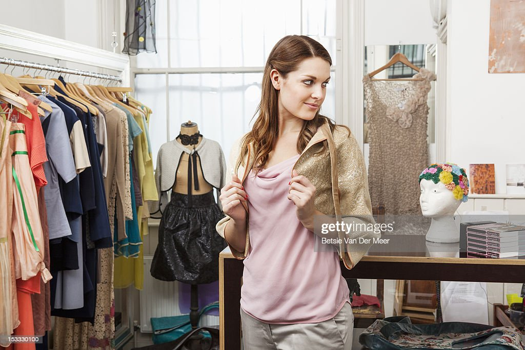 Woman trying on jacket in designer shop. : Stock Photo