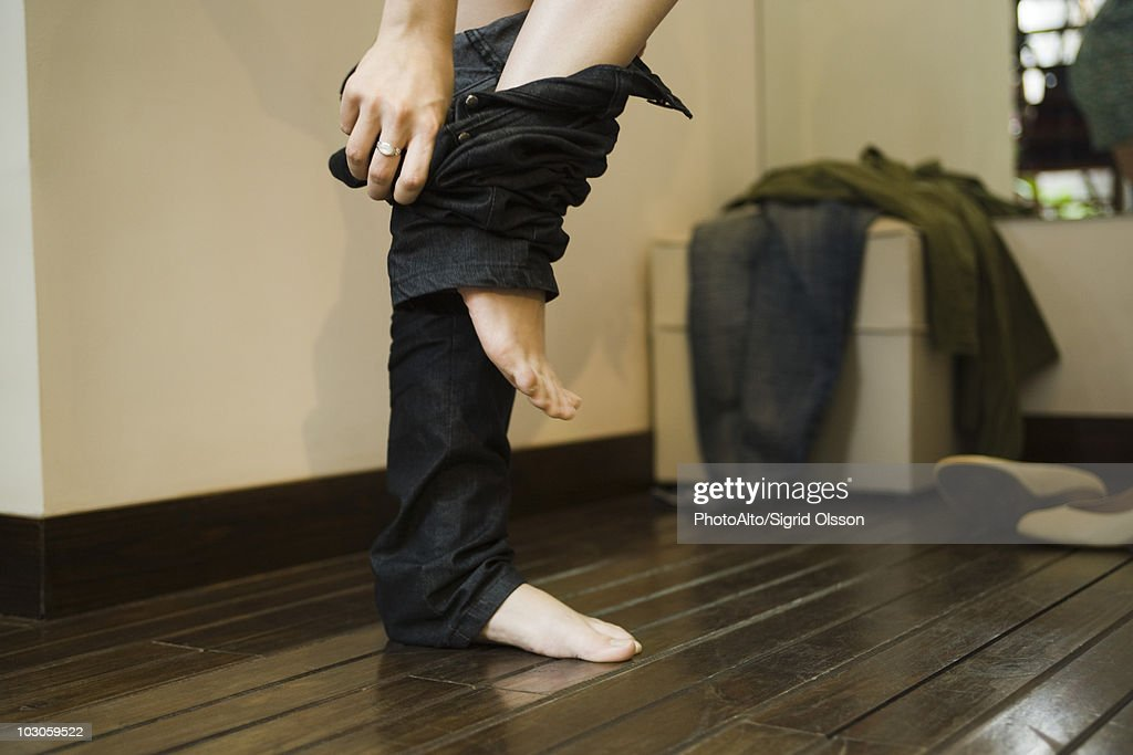 Woman trying on jeans in fitting room