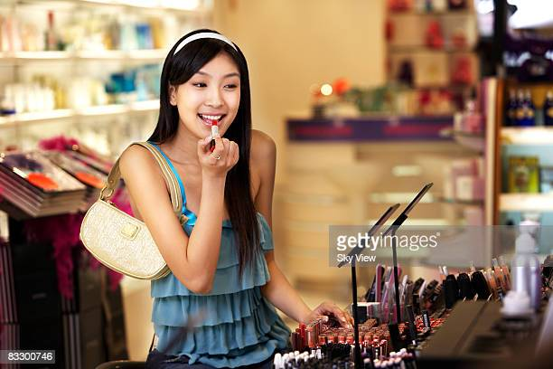 Woman trying on lipstick in retail store