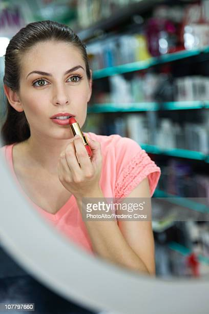 Woman trying on lipstick in store