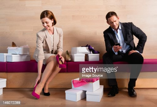 Woman trying on shoes in shoe shop, bored man texting