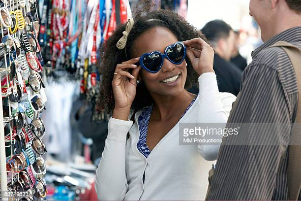 Woman trying on sunglasses with friend