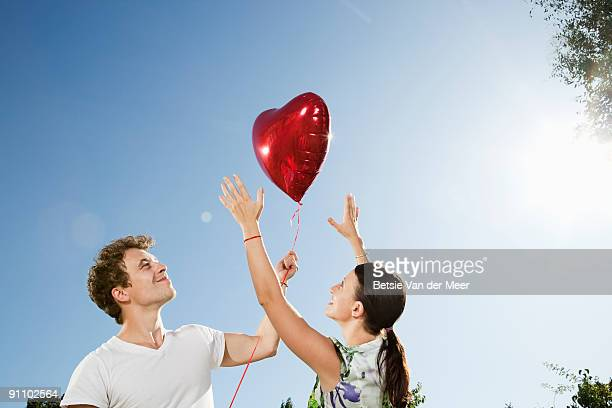 woman trying to catch men's heartshaped balloon