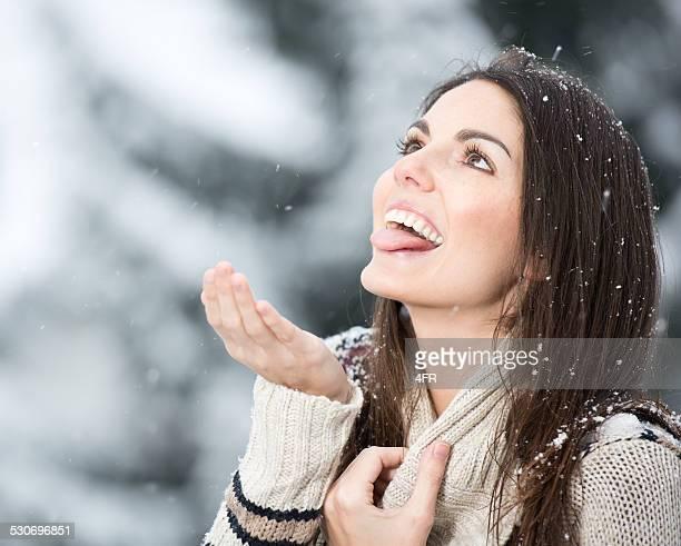Femme essayer d'attraper de flocons de neige avec sa languette