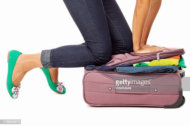 Woman Trying To Close Overfilled Suitcase - Isolated