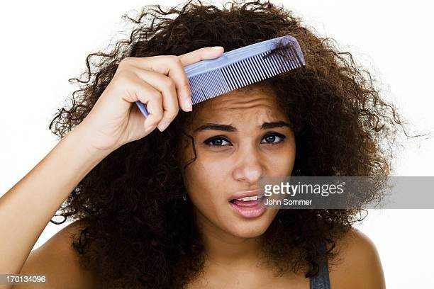 Woman trying to comb her frizzy hair