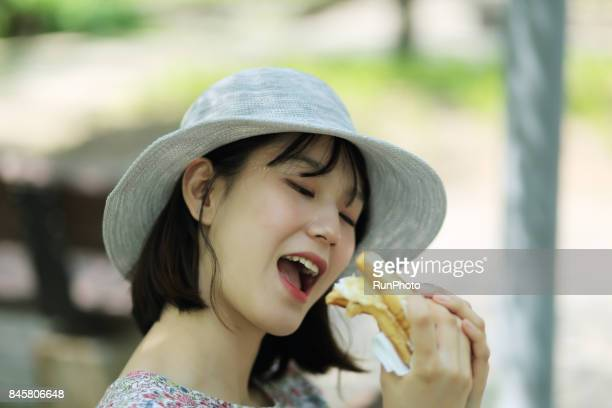 woman trying to eat bread with a smiling face