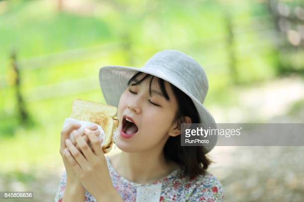 woman trying to eat while watching bread