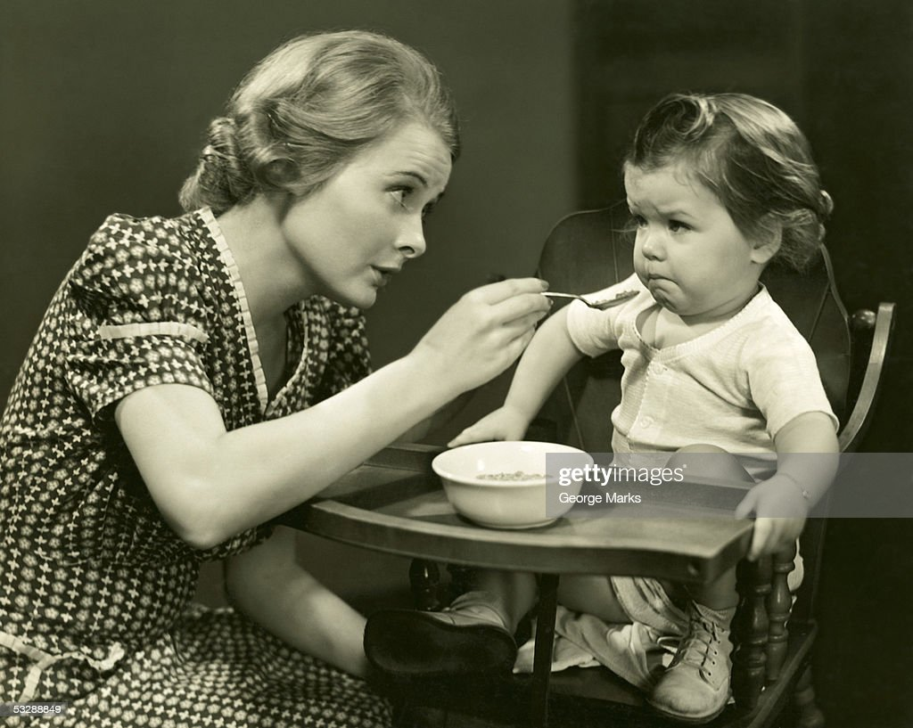 Woman trying to feed baby : Stock Photo